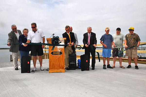 Pender County Commissioner George Brown, State Rep. Carolyn Justice, Pender County Commissioner David Williams, State Sen. Bill Rabon, Former NCWRC Chairman Steve Windham, Pender County Commissioner F.D. Rivenbark, Juston Bell, Robert Earl Best, and Walter Bell cut the ribbon at the opening of the new Hampstead Boating Access Area.