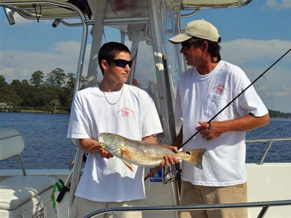 Capt. Mark Hoff and his son with a red drum.